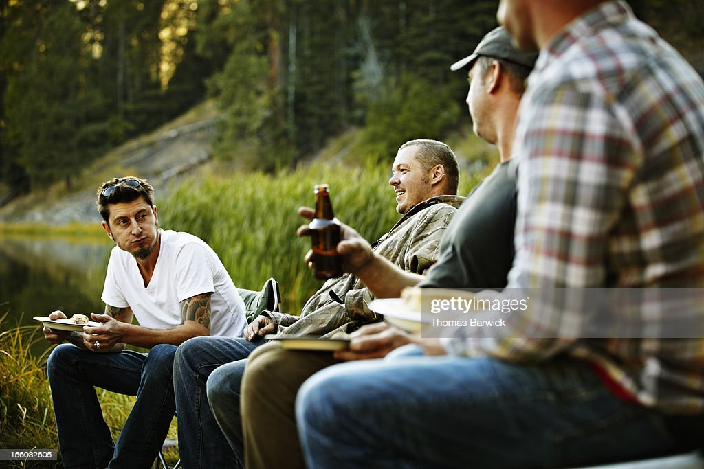Group of friends eating and drinking while camping : Stock Photo