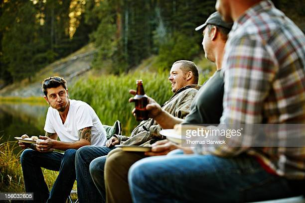 Group of friends eating and drinking while camping