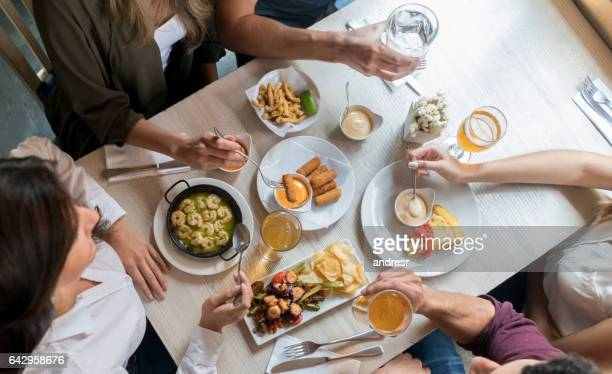 group of friends eating at a restaurant - tapas stock photos and pictures