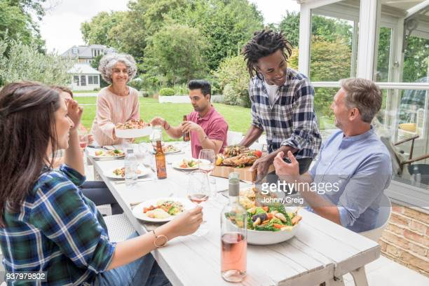 Group of friends eating dinner and chatting outside