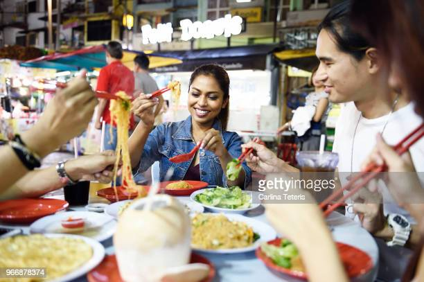 group of friends eating dinner at a night market table - malaysian culture stock pictures, royalty-free photos & images