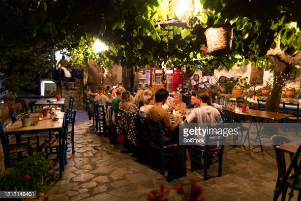 group of friends eating dinner in mediterranean courtyard - greece tourism stock pictures, royalty-free photos & images