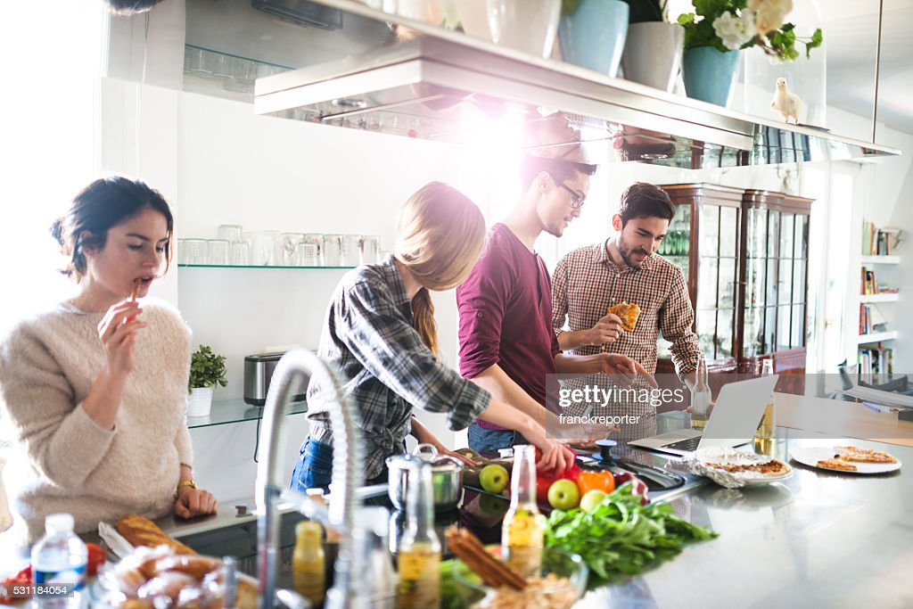 group of friends eating on the kitchen and preparing food : Stock Photo