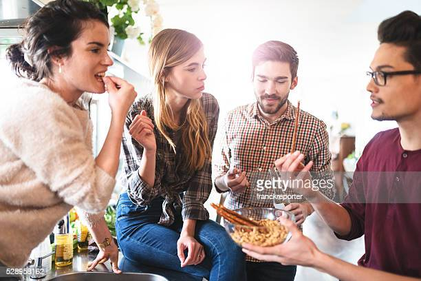 group of friends eating on the kitchen for the party