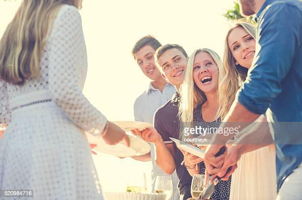 Grupo de amigos, comer ao ar livre.