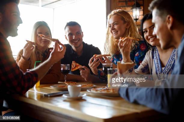 groep vrienden pizza eten in restaurant - koffie drank stockfoto's en -beelden