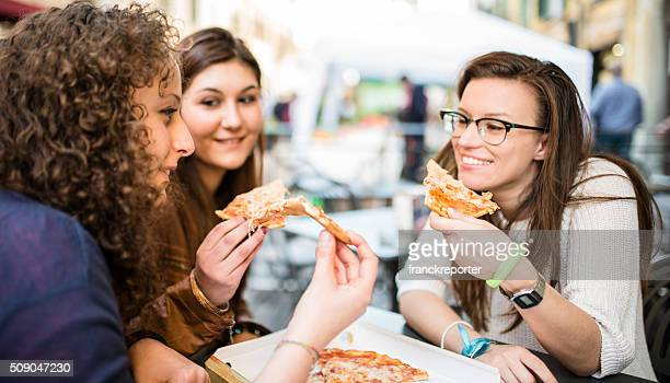 group of friends eating pizza togetherness at the fast food