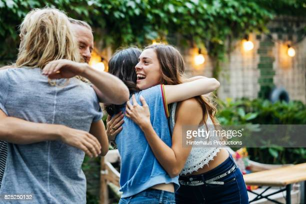 a group of friends embrace, excited to see each other at barbecue meetup - embracing stock pictures, royalty-free photos & images