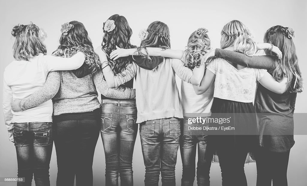 Group Of Friends Embracing Against Wall At Party : Stock Photo