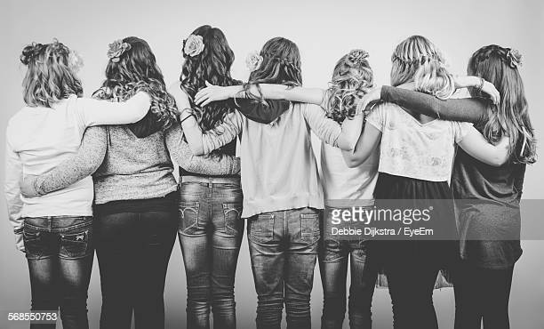 Group Of Friends Embracing Against Wall At Party
