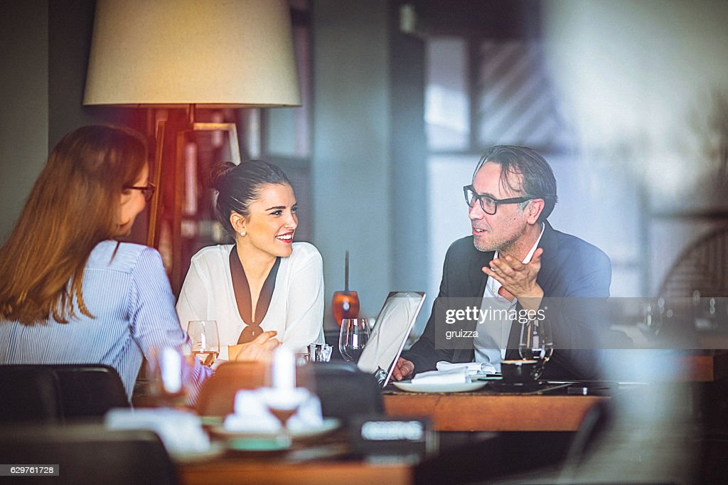 Group of friends enjoy chatting during lunch time at restaurant : Stock Photo
