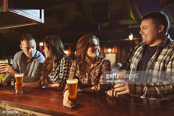 Group of friends enjoyin   Drinking beer  in the old pub