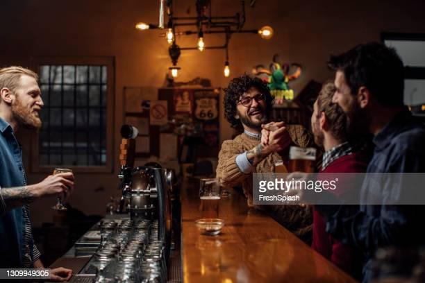 バーでビールのカップルを楽しむ友人のグループ, バーテンダーと一緒に笑う - アイルランド文化 ストックフォトと画像