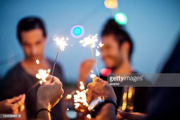 gruppe von freunden eine party auf der dachterrasse mit einem feuerwerk zu genießen - silvester stock-fotos und bilder
