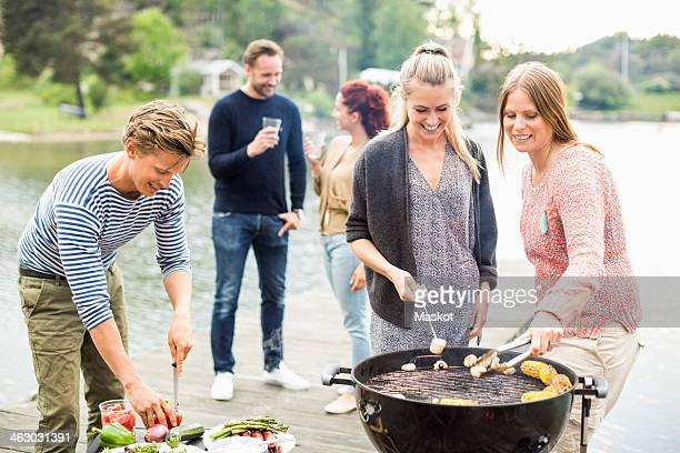 Group of friends enjoying barbecue party on pier