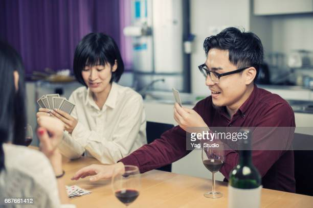 Group of friends enjoying card game at home.