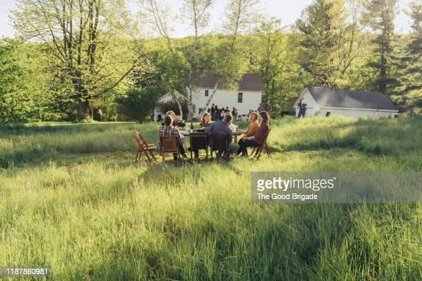 group of friends enjoying dinner in rustic field - tischflächen aufnahme stock-fotos und bilder