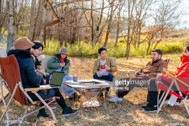冬の朝、キャンプ場で温かい飲み物を飲んで楽しむ友人のグループ - キャンプする ストックフォトと画像