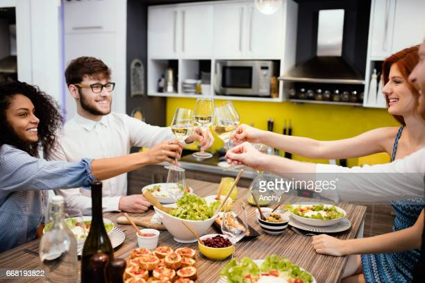 Gruppe von Freunden genießen Getränke beim Abendessen zu Hause