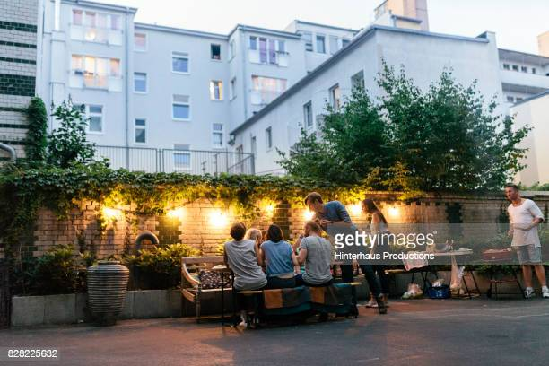 group of friends enjoying evening barbecue meal together - wohnung stock-fotos und bilder