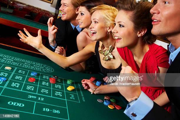 gruppe von freunden, die in einem casino - casino stock-fotos und bilder