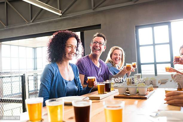 Group Of Friends Enjoying Lunch Together At A Brewery