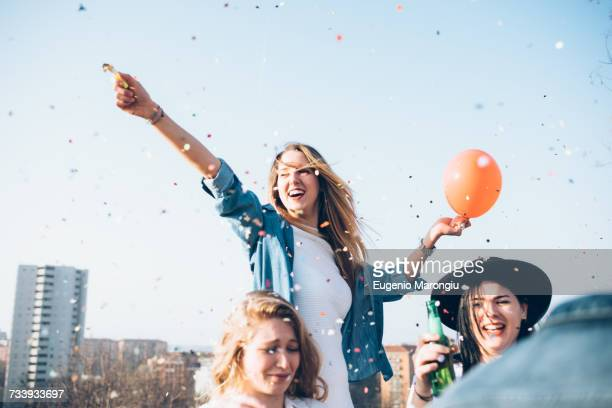 Group of friends enjoying roof party, confetti in air