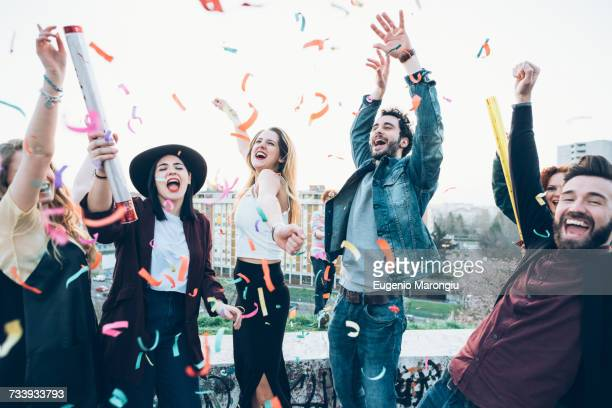 group of friends enjoying roof party, confetti in air - festeggiamento foto e immagini stock