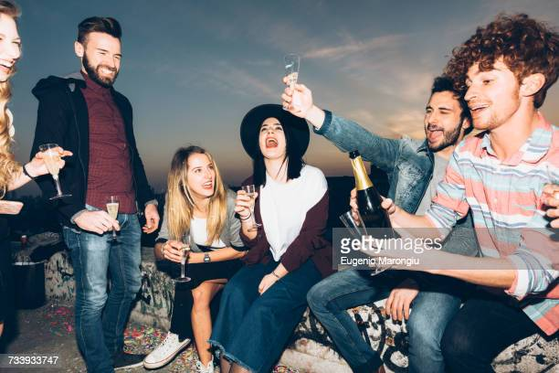 Group of friends enjoying roof party, holding champagne glasses, making a toast
