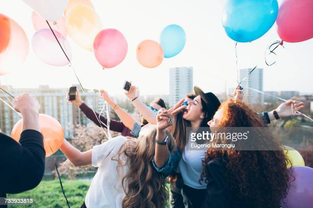 Group of friends enjoying roof party, holding helium balloons