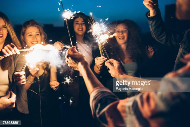 Group of friends enjoying roof party, holding lit sparklers