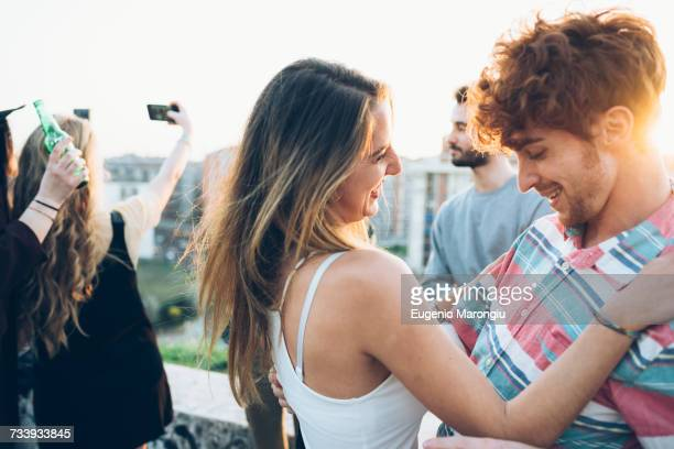 Group of friends enjoying roof party, young man and woman dancing together