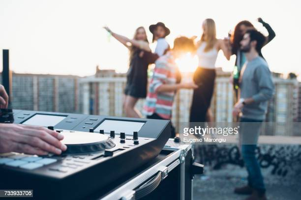 Group of friends enjoying roof party, young man using mixing desk