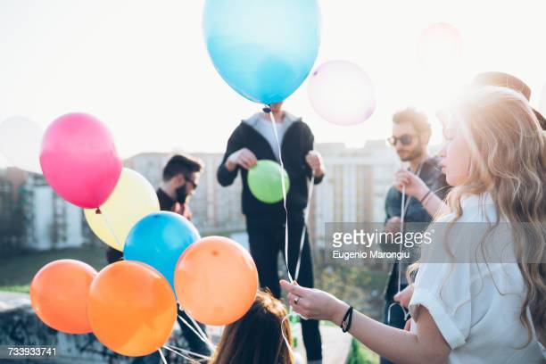 Group of friends enjoying roof party, young woman holding helium balloons