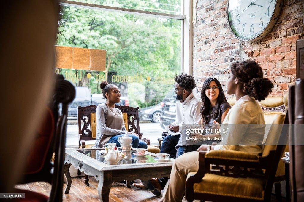 Group of friends enjoying tea at cool teashop : Stock Photo
