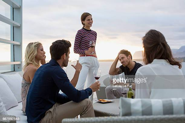 group of friends enjoying wine at a resort - eleganza foto e immagini stock