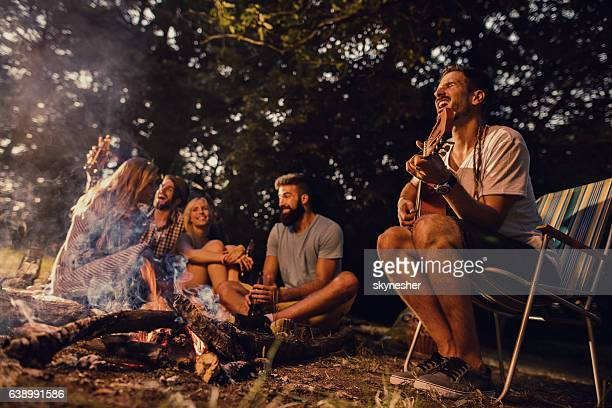 Group of friends enjoying with music around campfire in nature.