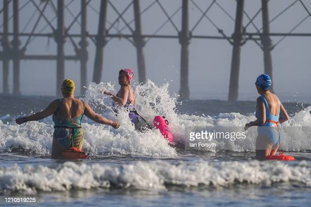 A group of friends enter the North Sea for a morning swim as the sun shines through sea fret on March 05 2020 in Saltburn By The Sea England As sea...