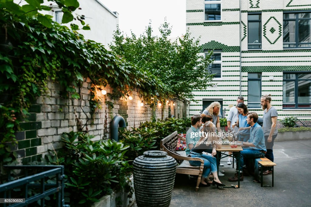 A Group Of Friends Gathered Around Table Preparing For Barbecue : Stock Photo