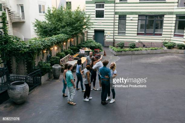 group of friends greeting each other at barbecue meetup - courtyard - fotografias e filmes do acervo