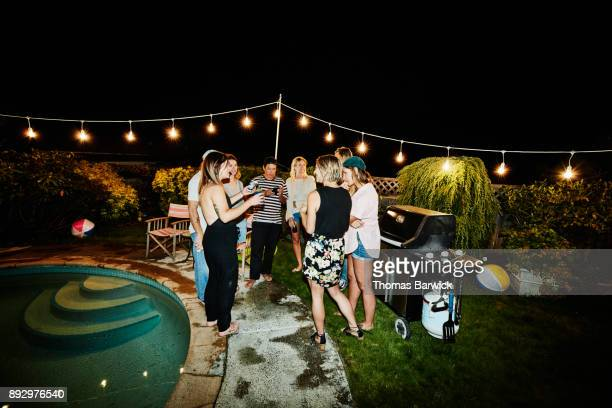 Group of friends hanging out in backyard during party on summer evening