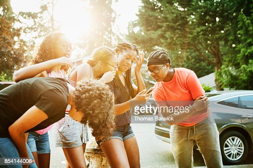 Group of friends hanging out in front yard looking at smartphone on summer evening