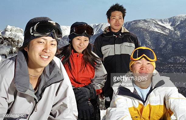 Group of friends hanging out on snowy slope, low angle view, portrait