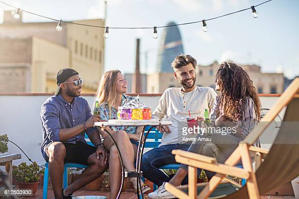 group of friends having a drink at rooftop party - cocktail party stock pictures, royalty-free photos & images