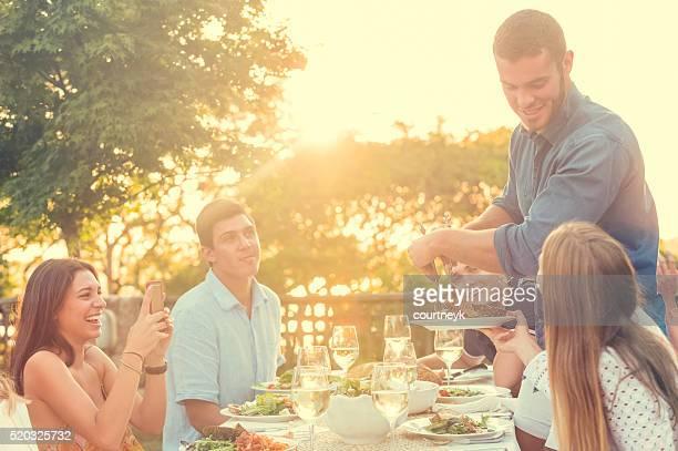 Gruppe von Freunden, die eine Mahlzeit im Freien.