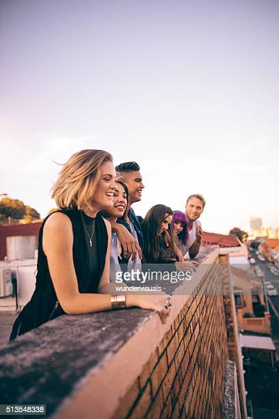 group of friends having a summer rooftop party at sunset - youth culture stock pictures, royalty-free photos & images