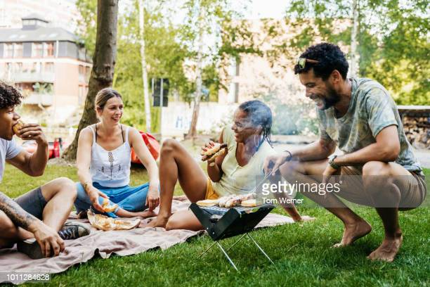 group of friends having bbq by canal - black shorts stock pictures, royalty-free photos & images