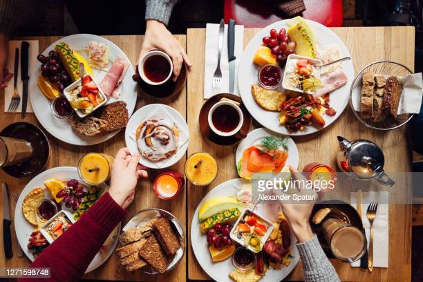 group of friends having celebration dinner together, directly above view - gourmet stock pictures, royalty-free photos & images