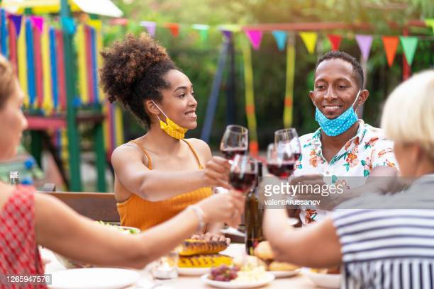 group of friends having dinner on back yard and wearing protective face mask, during covid-19 - dining stock pictures, royalty-free photos & images