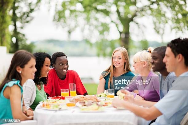 group of friends having dinner outside. - red shirt stock pictures, royalty-free photos & images